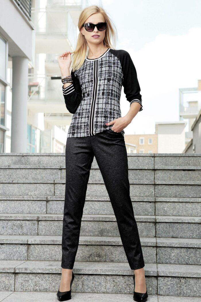 Kobieta stojąca na schodach ubrana w bluzkę w kratkę i czarne eleganckie spodnie